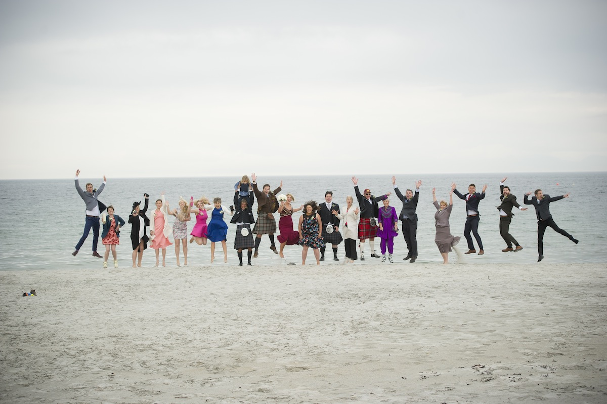 large-group-jumping-guests-beach-sea-horizon.jpg