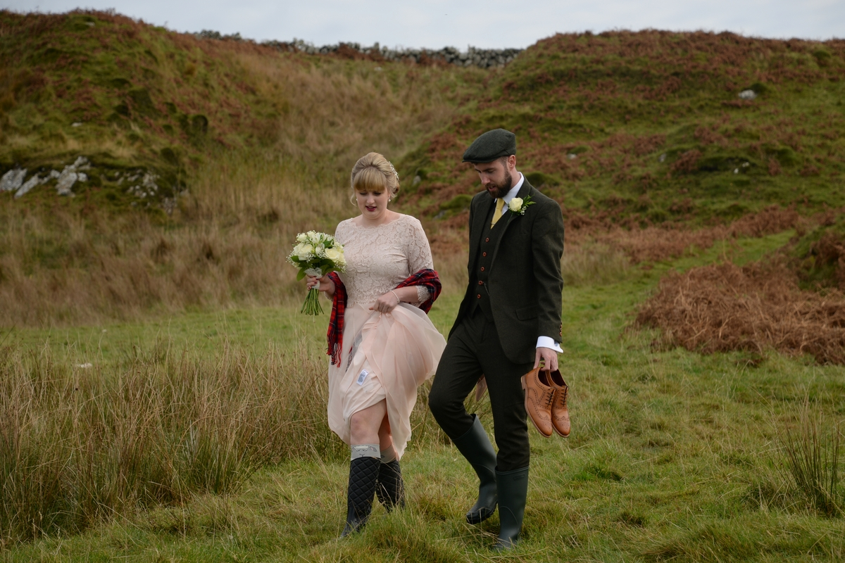 D-walking-couple-bride-groom-wellies-outside-countryside-shoes-cap.jpg
